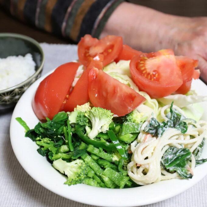 皿に山盛りのトマトやキャベツほうれん草などの緑黄色野菜のサラダ