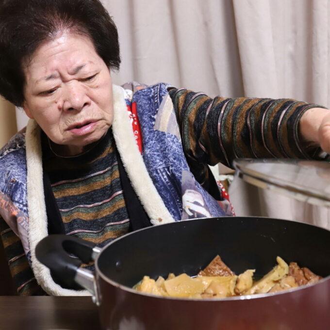 手作りの煮物の鍋のフタを開ける祖母(おばあ)