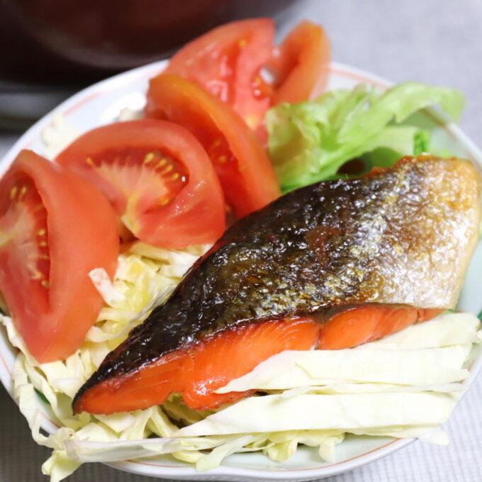 キャベツの上に乗せ、トマトを添えた焼き鮭