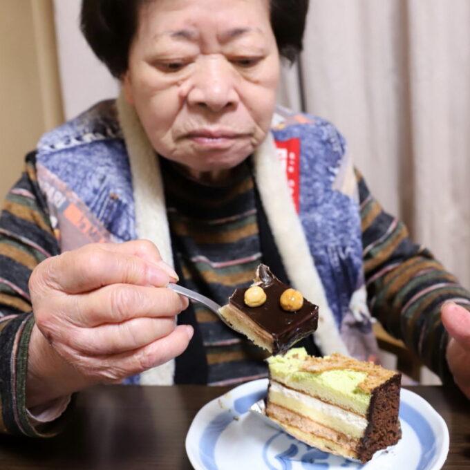 チョコレートケーキをスプーンですくって食べている祖母(おばあ)