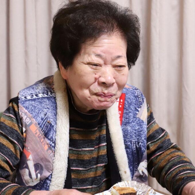 好物のケーキを食べて笑顔の祖母(おばあ)