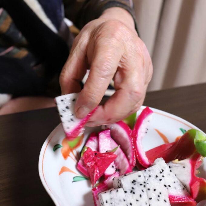祖母(おばあ)が摘まんでいる皿に盛りつけたドラゴンフルーツ
