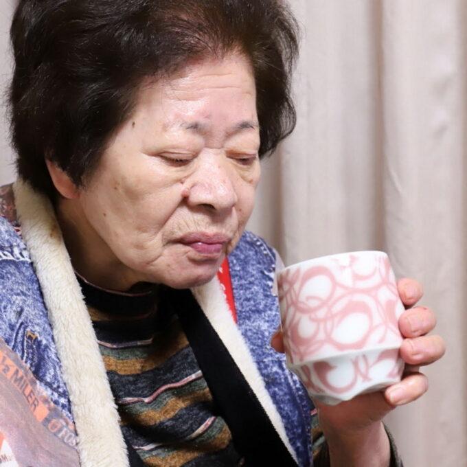 湯呑でお茶を飲んで息を吐く祖母