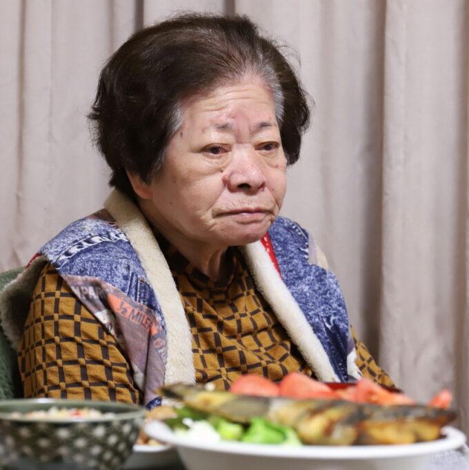 食卓に着いて遠くを見つめる祖母(おばあ)