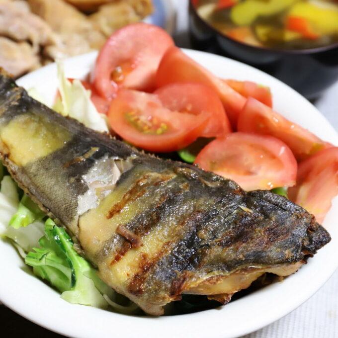 トマトやキャベツと一緒に盛られた焼き魚(縞ホッケ)
