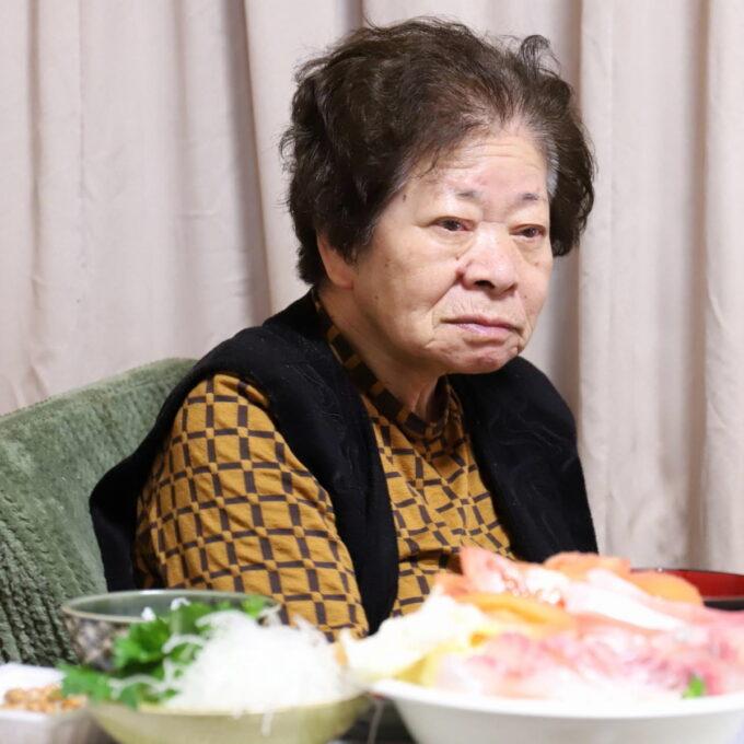 食卓に座ったまま遠くを見ている祖母(おばあ)