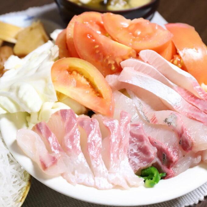 トマトやキャベツなどのサラダの上に刺身を乗せた晩ごはんのワンプレート