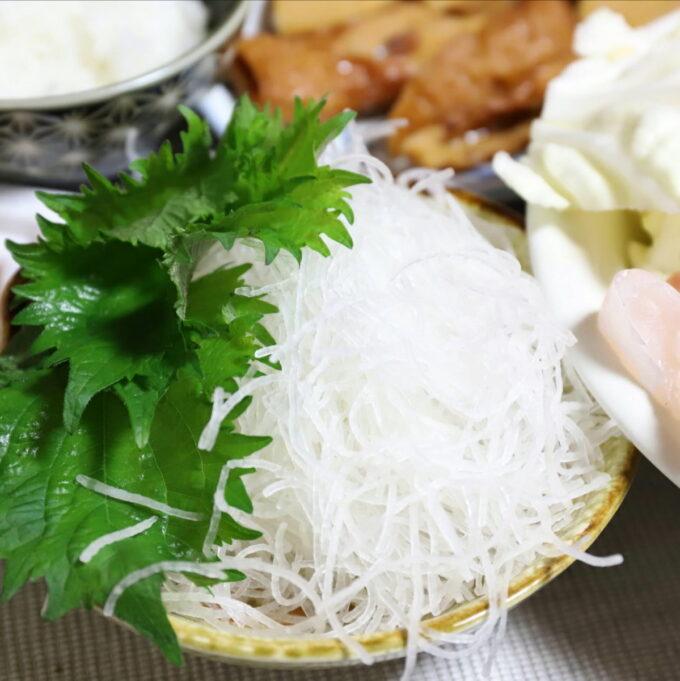 小皿に盛りつけた刺身のツマと大葉