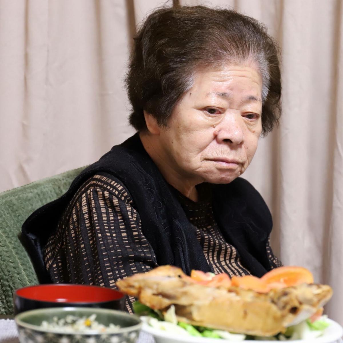 晩ごはんの食卓に着いた祖母(おばあ)