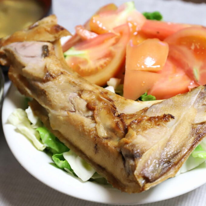 サラダと一緒に皿に盛りつけられた焼いたマグロのカマ