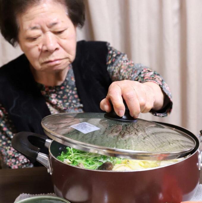 食卓に置いた鍋のフタを手で持って開けようとしている祖母(おばあ)