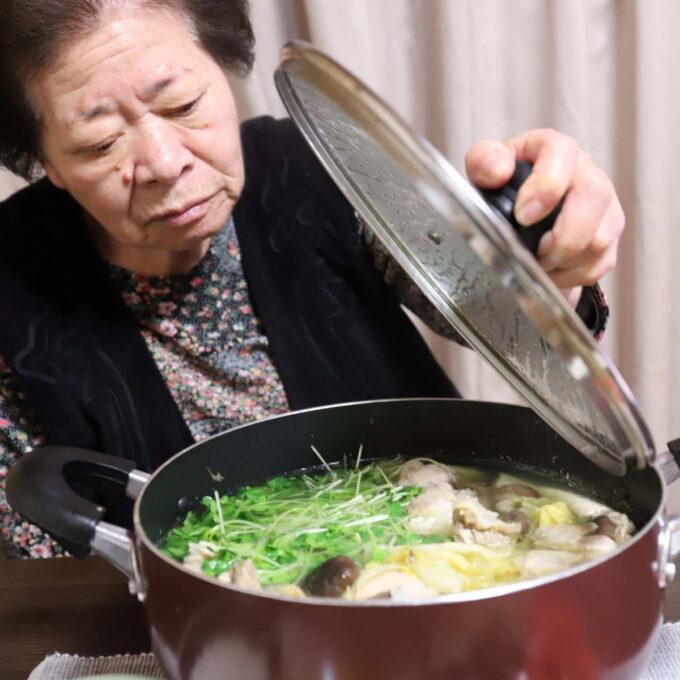 食卓の水炊きの鍋のフタを片手で持ち上げている祖母(おばあ)