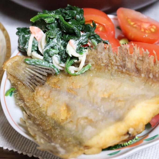 カレイのフライが野菜と一緒に皿に盛りつけられている