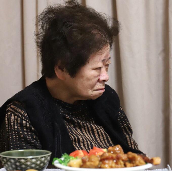 食卓に着いてテレビを見ている祖母(おばあ)