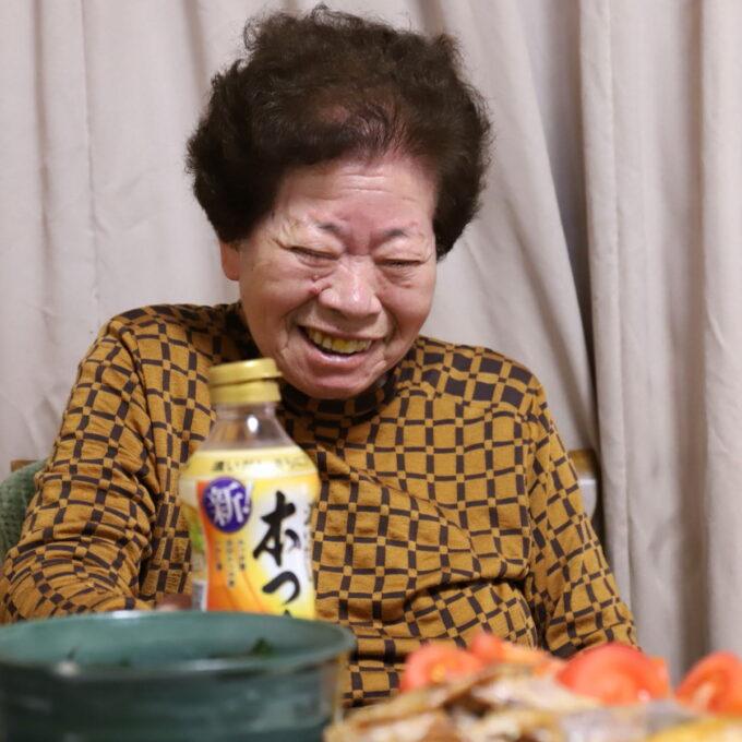 食卓に着いて笑っている祖母(おばあ)