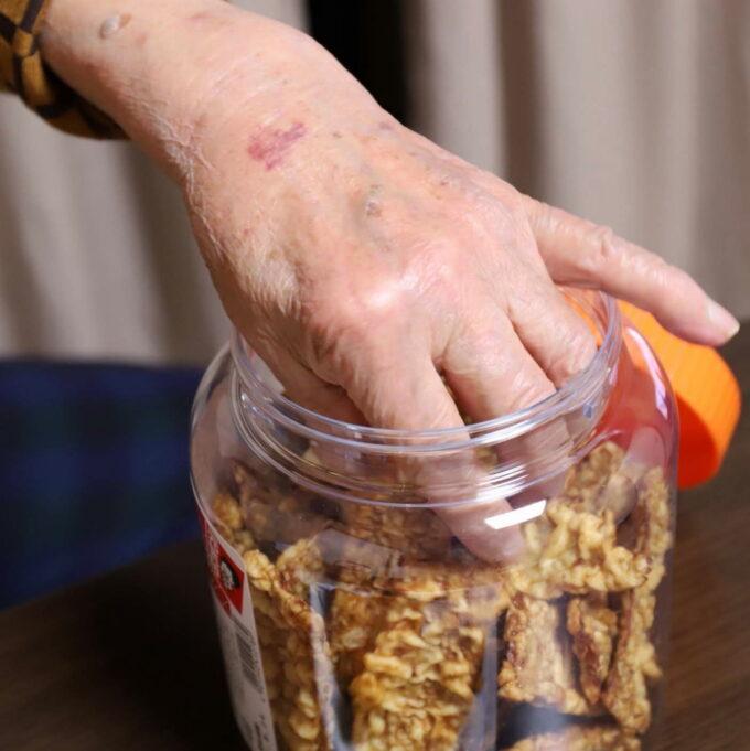 イカ天スナックを手で摘まんでボトルから取り出しているところ