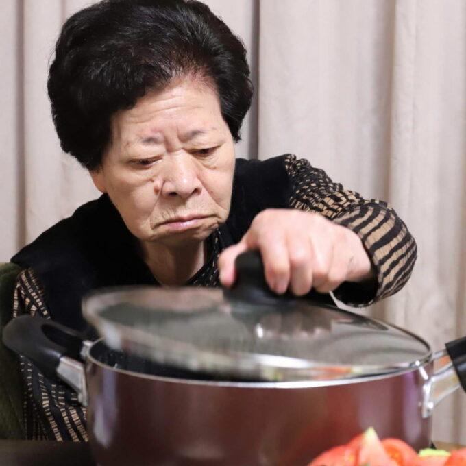 食卓に着いて鍋のフタに手をかけている祖母(おばあ)