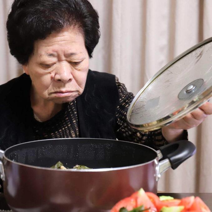 食卓に置いた鍋のフタを開けている祖母