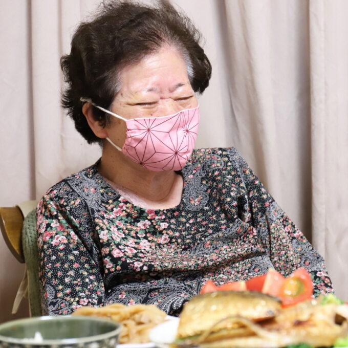 誕生日に鬼滅の刃の『禰豆子』柄のマスクをはめて、食卓について笑っている祖母(おばあ)