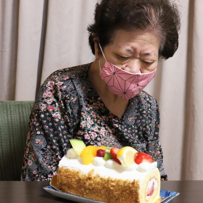 孫が買ってきた誕生日ケーキを見つめる祖母
