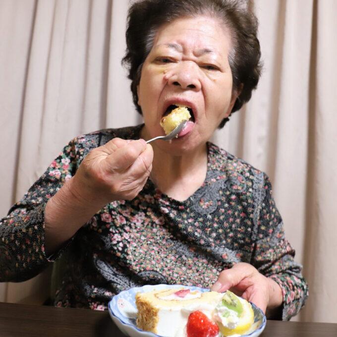 大口を開けてケーキを食べる87歳の祖母(おばあ)