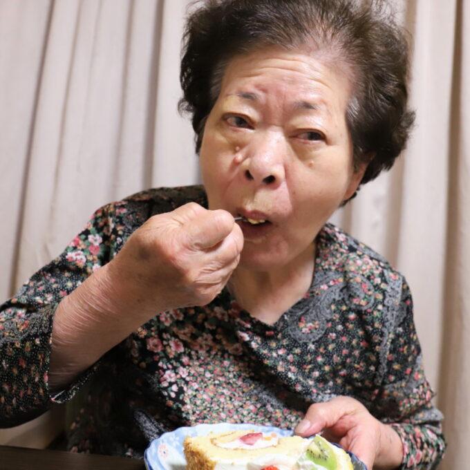 誕生日ケーキを頬張る祖母(おばあ)