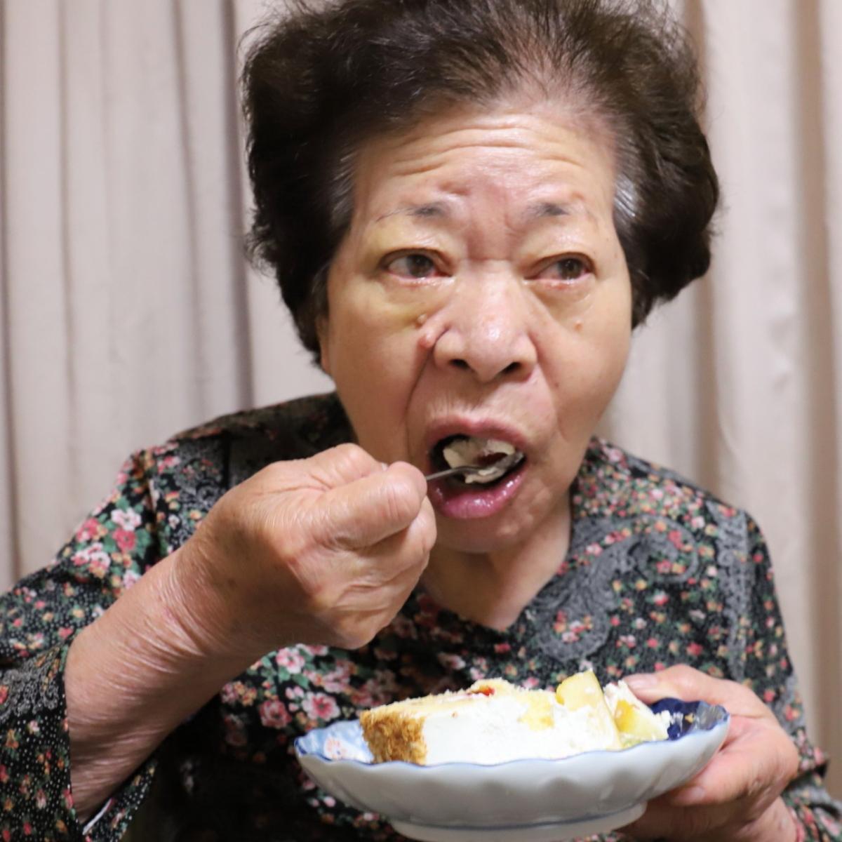 誕生日ケーキの皿を抱えて食べている祖母