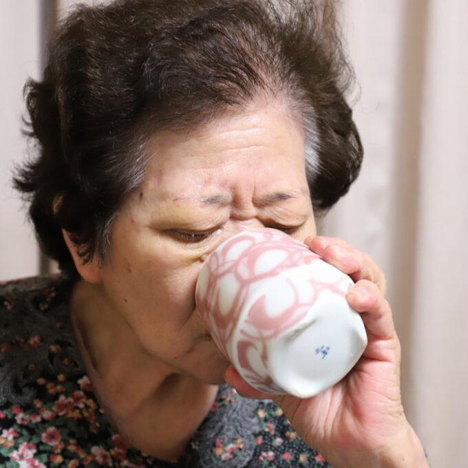 誕生日ケーキを食べ終えて、お茶を飲む祖母(おばあ)
