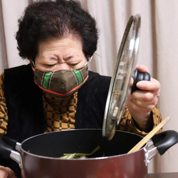 鍋のフタを開ける、マスクをしている祖母