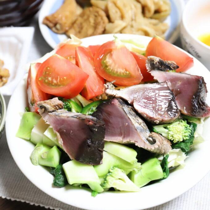 カツオのたたきとトマトやブロッコリーなどの野菜が、一緒に皿に盛られたサラダと魚のワンプレート