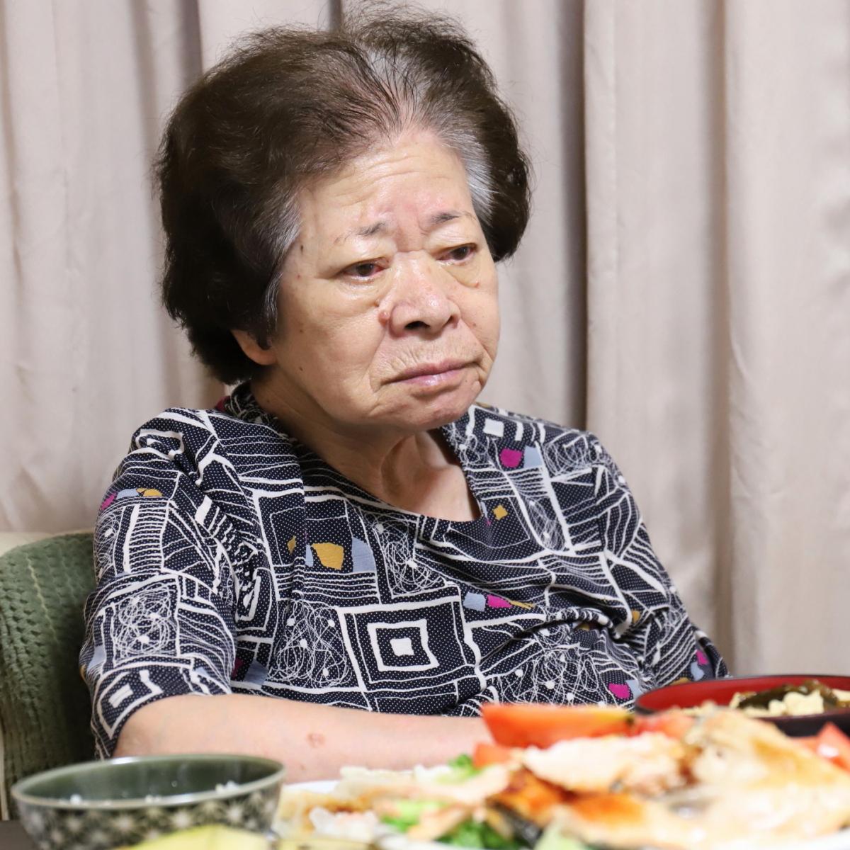 晩ごはんを用意して疲れた顔で遠くを見ている祖母(おばあ)