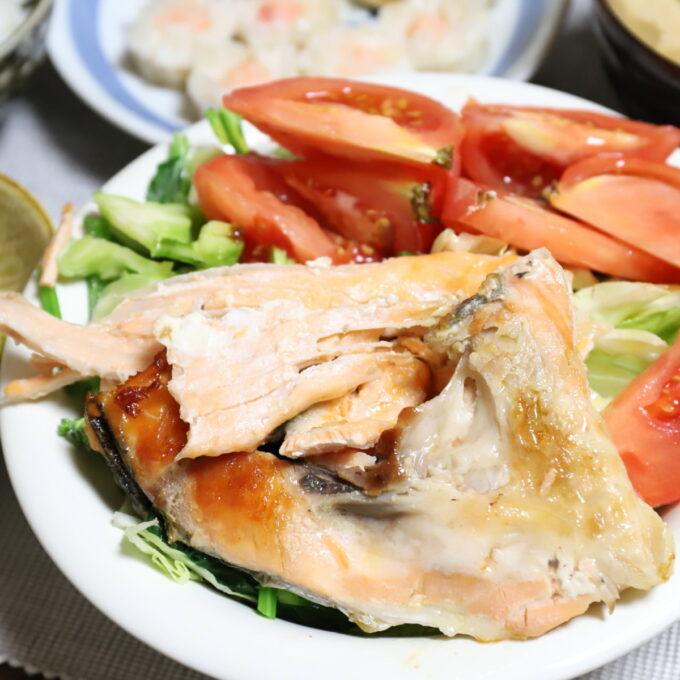 トマトやレタスなどのサラダの上に鮭のアラを乗せたワンプレート