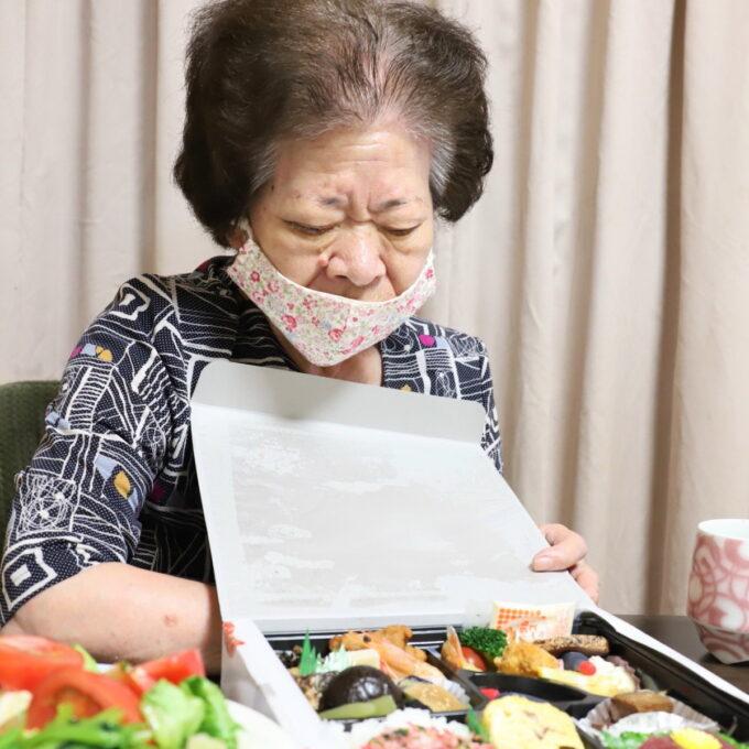 仕出し弁当のフタを開ける、マスクをした祖母(おばあ)