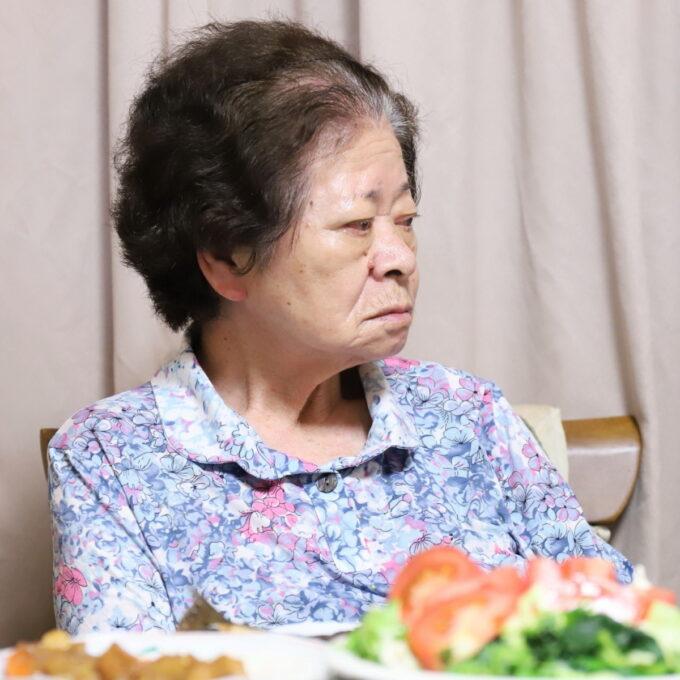 晩ごはんを用意して席に着いている祖母(おばあ)
