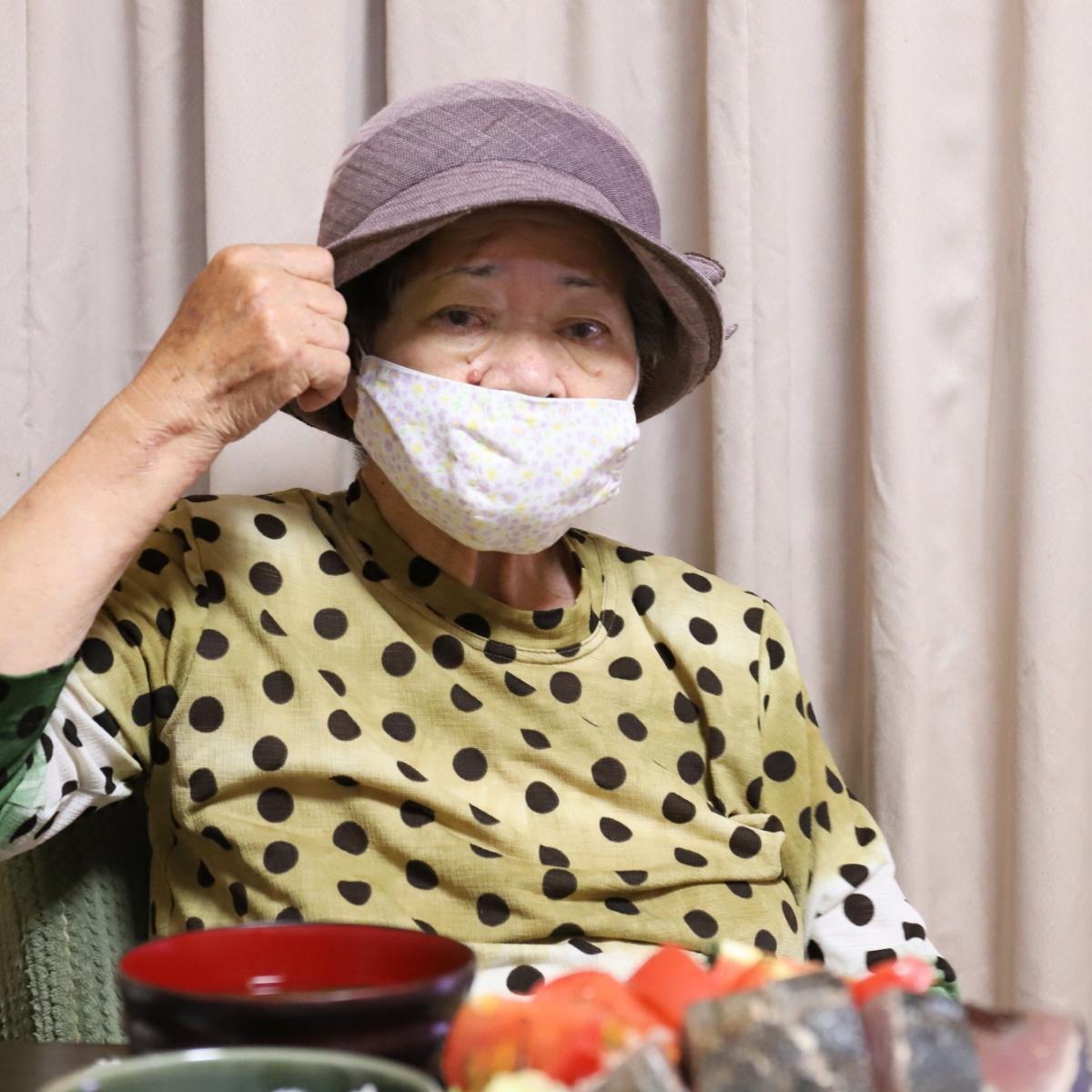 おしゃれな夏用の帽子をかぶり食卓に着く祖母・おばあ