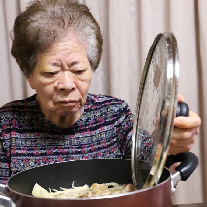 食卓の上の鍋のフタを持ち上げる祖母・おばあ