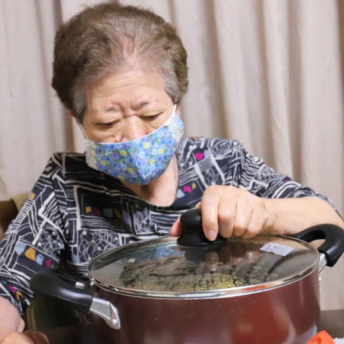 食卓に置いた鍋のフタを片手で掴む祖母(おばあ)