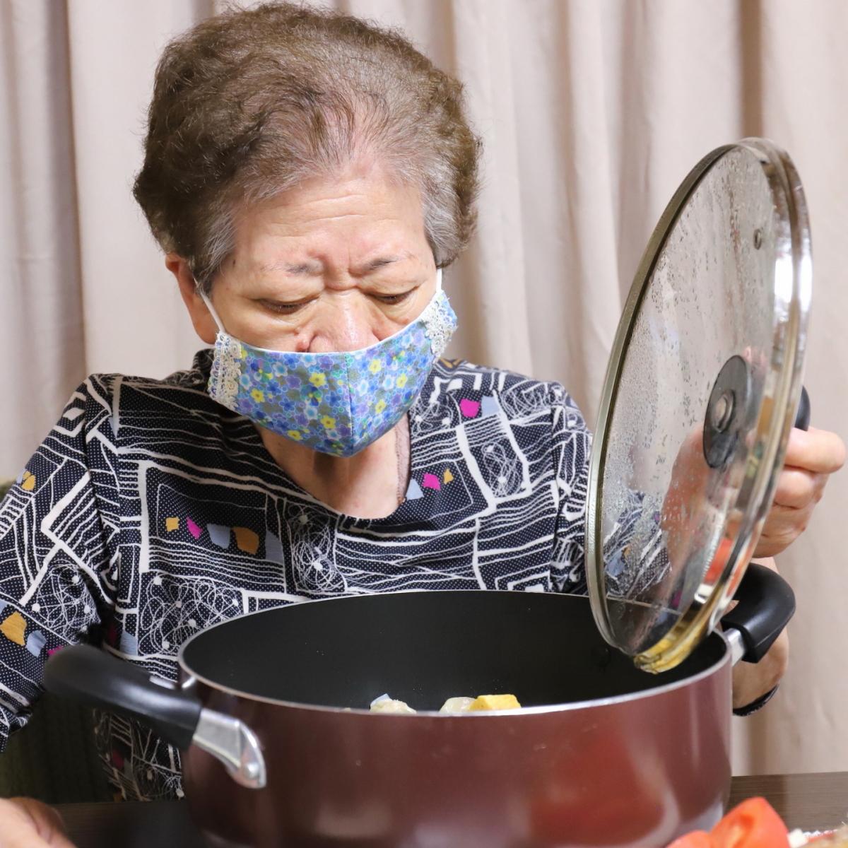食卓に置いた鍋のフタを開ける祖母(おばあ)