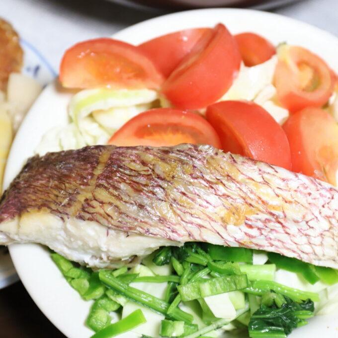 トマトやほうれん草などのサラダの上に焼いた鯛の切り身を乗せたワンプレート
