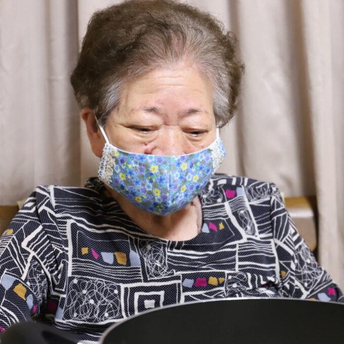 マスクをして食卓に着いている祖母(おばあ)