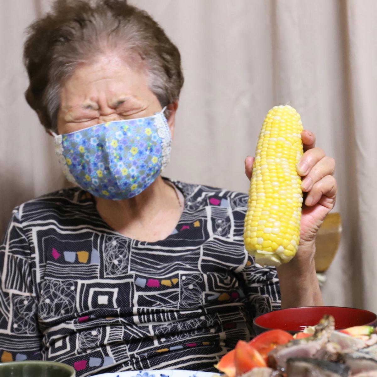トウモロコシを手に持つマスクをした祖母(おばあ)