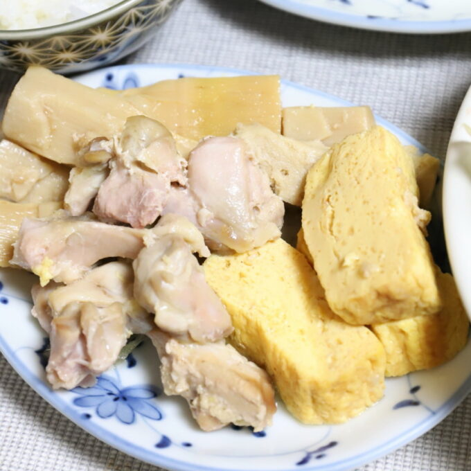 皿に盛った出汁巻き玉子と鶏肉とタケノコの煮物