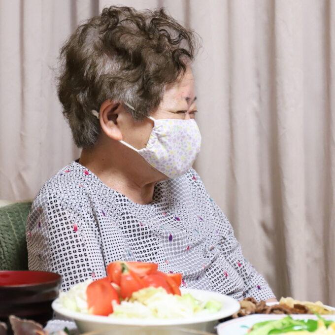 マスクを着けて横を向く笑顔の祖母