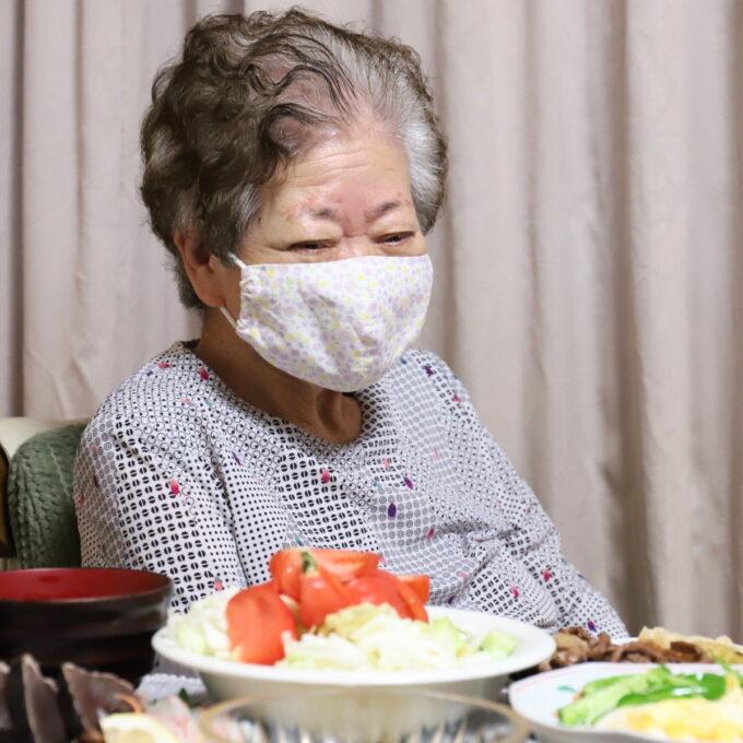 食卓に着いてマスクを着けている祖母・おばあ