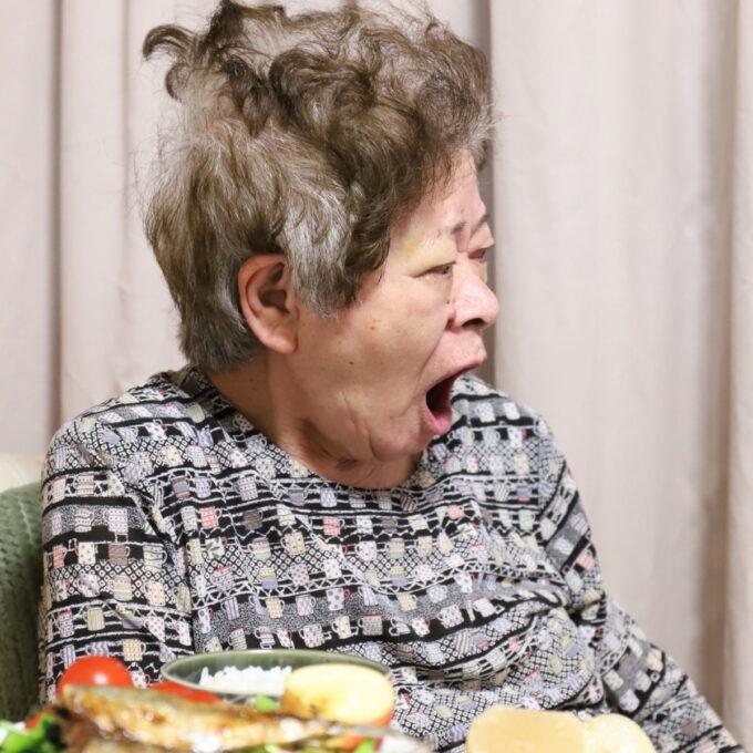 食卓に着いてあくびをする祖母・おばあ