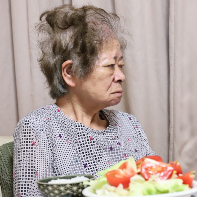 夕飯の食卓に着いて横を向いている祖母・おばあ