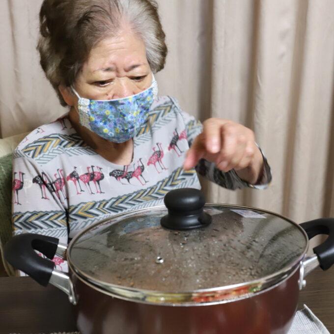 テーブルに乗った大きな鍋と食卓に着いた祖母・おばあ