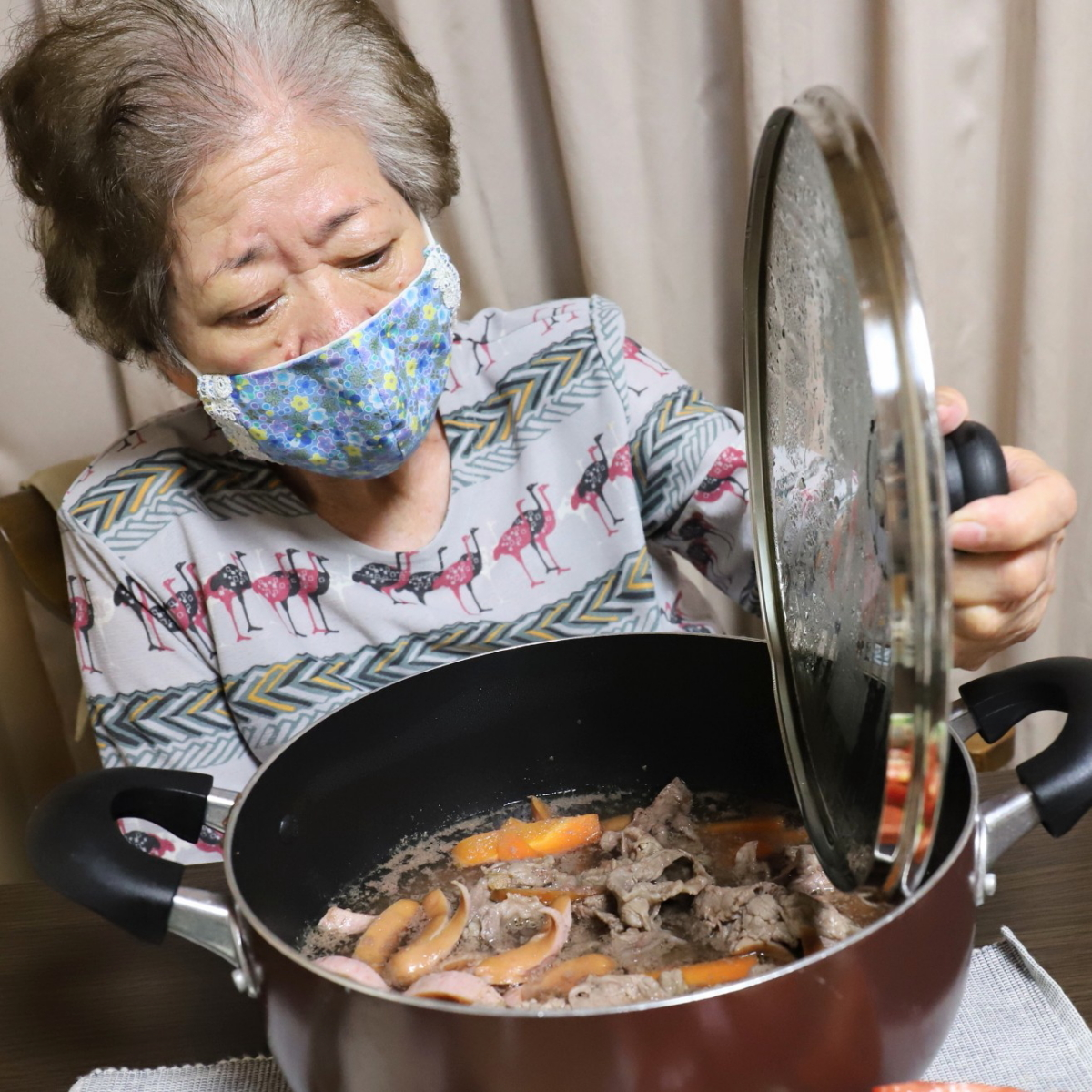 食卓に着いて、鍋のフタを開けている祖母・おばあ