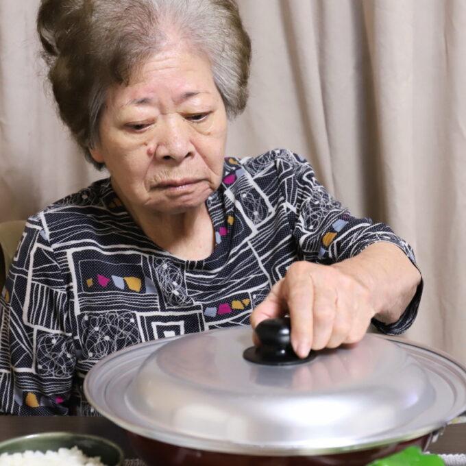 フライパンのフタに手を伸ばしている祖母・おばあ