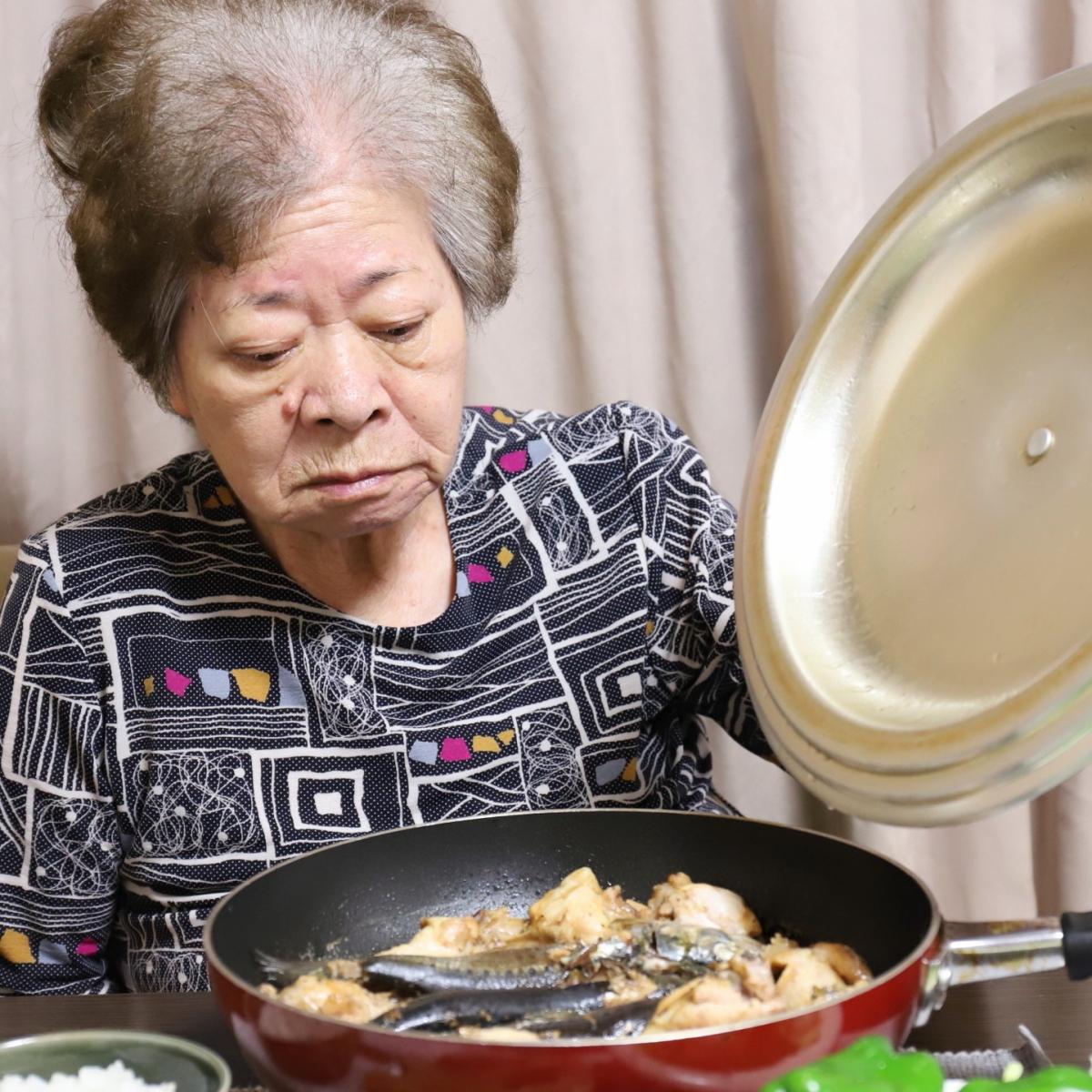 食卓でフライパンのフタを開けている祖母・おばあ